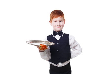 servant: Little smiling waiter stands with empty tray serving something. Redhead child boy in suit plays restaurant servant isolated at white background