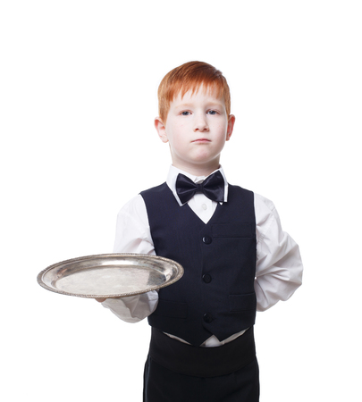 servant: Little waiter stands with empty tray serving something. Redhead child boy in suit plays restaurant servant at blue background