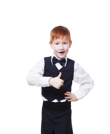 welldressed: Little cute redhead boy in vest with bow tie shows thumb up. Portrait of well-dressed child in bow tie, approval,, satisfaction gesture. Kid isolated on white background