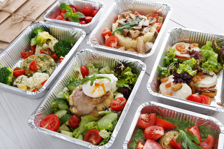 Healthy food restaurant delivery and diet concept. Take away of fitness meal. Weight loss lunch in foil boxes. Poached egg with steak and other dishes at white wood