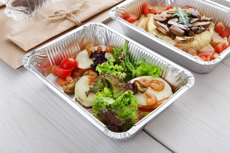 eat right: Healthy food and diet concept. Take away of fitness meal. Weight loss nutrition in foil boxes. Vegetables, lettuce and mozarella cheese with cherry tomatoes and shrimps closeup at white wood Stock Photo