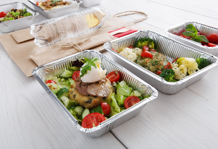 eat right: Healthy food restaurant delivery and diet concept. Take away of fitness meal. Weight loss lunch in foil boxes. Poached egg with steak, paper bag, water bottle and other dishes at white wood