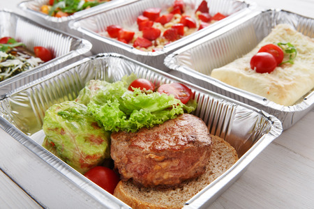 eat right: Healthy food background. Take away of natural organic food in foil boxes. Fitness nutrition, meat steak, vegetables and berry cereal. Top view, flat lay.