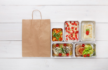 eat right: Healthy food delivery, daily meals and snacks. Diet nutrition, vegetables, meat and fruits in foil boxes and brown paper bag package. Top view, flat lay at white wood with copy space