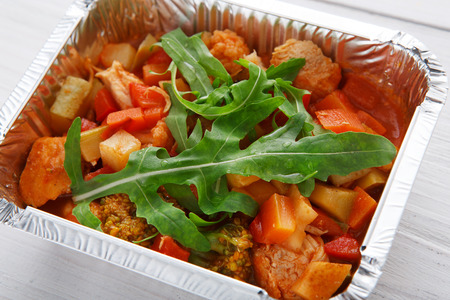 eat right: Healthy food and diet concept. Take away of fitness meal. Weight loss nutrition in foil box. Vegetable stew with soy meat, tomato sauce and arugula closeup at white wood