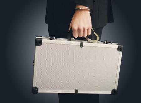 hand guard: Bank finance security concept - businessman or guard hand in handcuffs closeup holding suitcase with money isolated at dark background