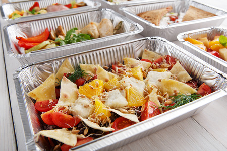 eat right: Healthy food and diet concept, restaurant dish delivery. Take away of fitness meal. Weight loss nutrition in foil boxes. Salad with cod fish, wheat sprouts and crispy tortilla pieces at white wood Stock Photo