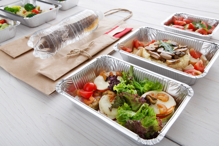 eat right: Healthy food and diet concept. Take away of fitness meal. Weight loss nutrition in foil boxes. Vegetables, lettuce and mozarella cheese with shrimps, paper bag and water bottle at white wood