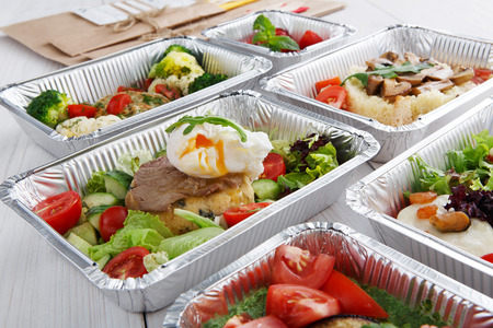 eat right: Healthy food restaurant delivery and diet concept. Take away of fitness meal. Weight loss lunch in foil boxes. Poached egg with steak and other dishes at white wood