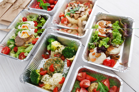 eat right: Healthy food restaurant delivery and diet concept. Take away of fitness meal. Weight loss lunch in foil boxes. Vegetable patty with caulifliwers, cherry tomatoes and broccoli closeup at white wood