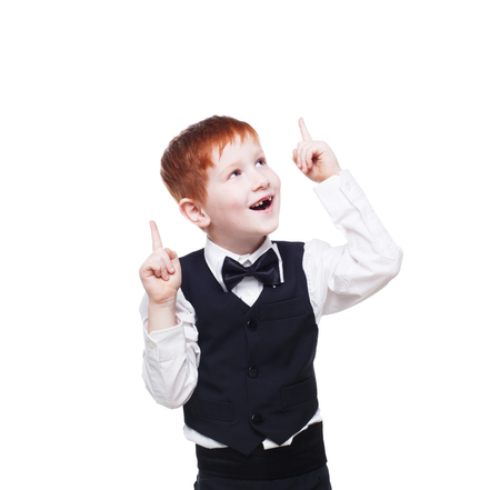 finger bow: Little cute happy redhead boy in vest with bow tie has an idea. Portrait of well-dressed emotional child show finger up as eureka sign, isolated on white background