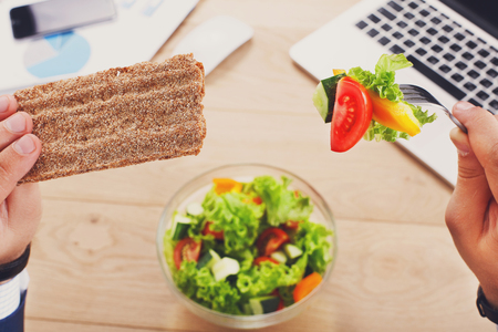 Business lunch at working place. Businessman in office. Healthy, diet food, vegetable salad with crispy yeast free bread. Hands of eating with fork man closeup, selective focus. Top view
