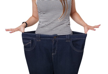 weight loss success: Unrecognizable woman torso, showing diet results isolated on white. Weight loss success, big size jeans on slim figure. Good shape, healthy lifestyle and eating right concept.