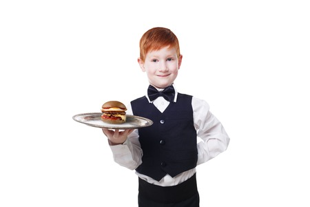 servant: Little waiter stands with tray serving hamburger. Redhead child boy in suit plays restaurant servant, gives burger isolated at white background Stock Photo