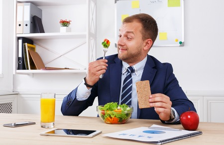 eating right: Man has healthy business lunch in modern office interior. Young handsome businessman at working place, looking at fork with vegetable salad in bowl, diet and eating right concept. Stock Photo