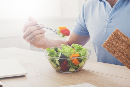 eating right: Unrecognizable man has healthy business lunch in modern office. Businessman in t-shirt at working place with vegetable salad in bowl and fork in hand, diet and eating right concept. High key