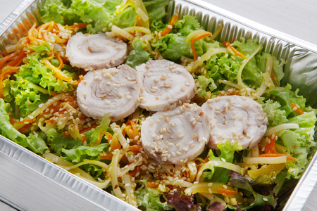 eat right: Healthy food and diet concept, restaurant dish delivery. Take away of fitness meal. Weight loss nutrition in foil boxes. Vegetable salad with sprouts and fish rolls closeup at white wood
