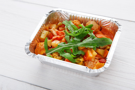 eat right: Healthy food and diet concept. Take away of fitness meal. Weight loss nutrition in foil box. Vegetable stew with soy meat, tomato sauce and arugula at white wood