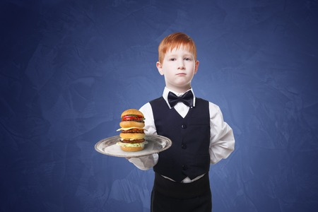 servant: Little waiter stands with tray serving big double hamburger. Redhead Child boy in suit plays restaurant servant, gives burger at blue background