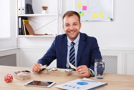 eating right: Man has healthy business lunch in modern office interior. Young handsome businessman at working place, looking at camera with vegetable salad in bowl, diet and eating right concept.