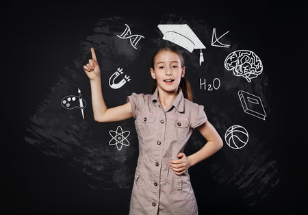 girl studying: Small girl in imaginary graduation cap has an idea. Child shows finger up as eureka sign. Smart schoolgirl studio portrait near chalkboard with education icons. Studying and getting knowledge concept.