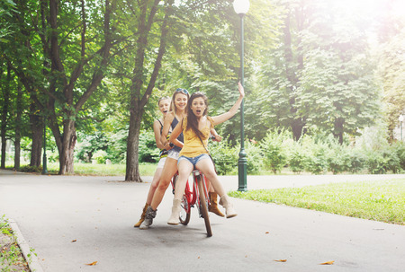 tonto: Happy boho chic stylish girls ride together having fun. Beautiful women on bicycles with basket full of wild flower. Female friends, youth and happiness, active summer leisure in park concept. Foto de archivo
