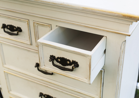 furniture detail: Old wooden antique chest of drawers with metal handles closeup, open drawer shelf. Shabby chic vintage style interior, furniture detail from rustic white wood. Stock Photo