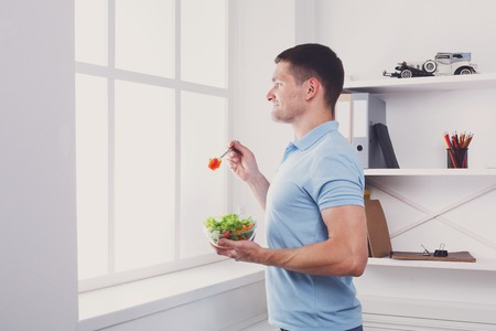 eating right: Man has healthy business lunch in modern office interior. Young handsome businessman profile portrait looking at window with vegetable salad in bowl, diet and eating right concept. High key image