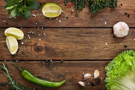 Green fresh food background on rustic wood top view with copy space. Wood planks and vegetables, cooking ingredients flat lay. Cooking concept, lime, lettuce, garlic, chili pepper, rosemary and mint. Stock Photo