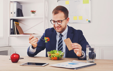 eating right: Man has healthy business lunch in modern office interior. Young handsome businessman in eyeglasses at working place, looking at plate with vegetable salad in bowl, diet and eating right concept.