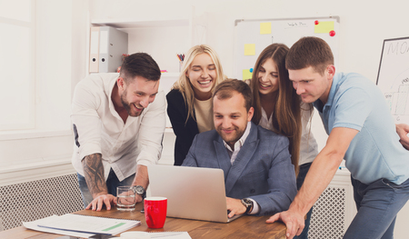 Happy smiling business people looking at laptop screen in the office. Successful corporate team of female and male coworkers check internet site of company together, partners and colleagues. Stock Photo