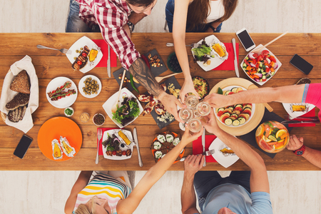 clink: People clink glasses, saying cheers, eat healthy meals at party dinner table. Friends celebrate with organic food, ratatoille and corn barbecue on wooden table top view. Woman pass dish plate to man