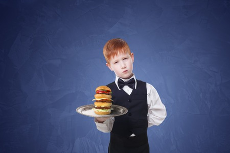 servant: Little sad and tire waiter stands with tray serving big double hamburger. Redhead child boy in suit plays hardworking restaurant servant, gives burger at blue background