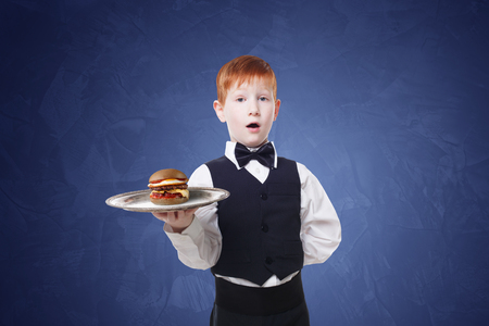 servant: Little surprised waiter stands with tray serving hamburger. Redhead child boy in suit plays restaurant servant, gives burger at blue background