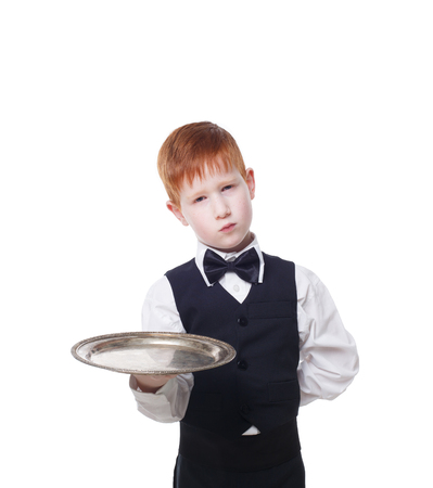 servant: Little sad and tire waiter stands with empty tray serving. Redhead child boy in suit plays hardworking restaurant servant at blue background