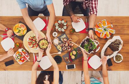 La gente come comidas saludables en la mesa de fiesta sirvió para el partido. Amigos celebran con comida orgánica en madera vista superior de la mesa. Paso de la Mujer plato placa para el hombre