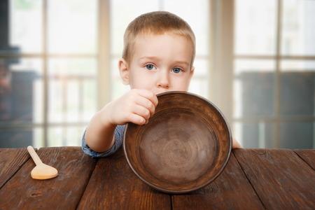 아동 기아 개념. 작은 유아 소년 나무 숟가락과 어두운 나무 테이블에 앉아 빈 그릇을 보여줍니다. 귀여운 아이 판에는 음식이 없습니다