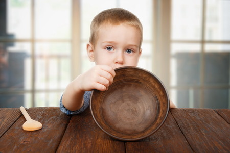 Child hunger concept. Small toddler boy shows empty bowl sitting at dark wood table with wooden spoon. Cute child has no food in plate