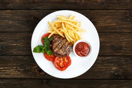 Restaurant eten - rundvlees gegrilde biefstuk met frietjes op een witte plaat. Geroosterde vlees en chips met gegrilde tomaten en kom barbecue saus, bovenaanzicht op houten tafel Stockfoto