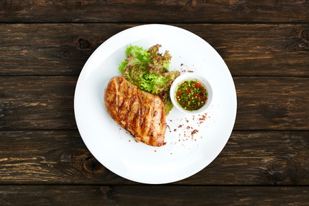 Restaurant food - chicken fillet grilled steak on wooden table background. Big piece of meat with lettuce on white round plate top view
