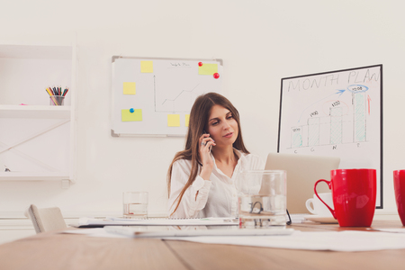 answer phone: Beautiful young businesswoman talking, answer a call at mobile phone, sitting at wooden desk with laptop and red cup. Modern office worker in white room. Succesfull woman, female carreer concept.