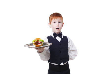 servant: Little surprised waiter stands with tray serving hamburger. Redhead child boy in suit plays restaurant servant, gives burger isolated at white background