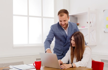 execution: Businessman supervising his assistants work on the laptop computer. Man helps woman in the office. Male boss and female secretary. Communication of manager and staff, checking job execution