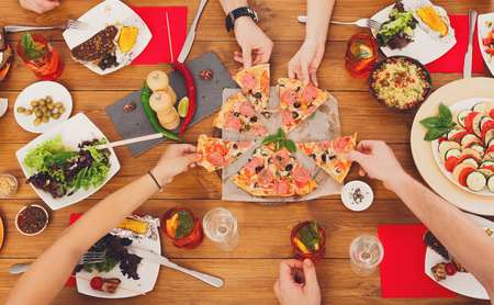 food and drink: People eat pizza at festive table served for party. Friends celebrate with catering food on wooden table top view. Woman and mans yands take the pieces of italian pizza. Stock Photo