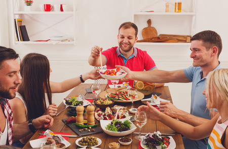 clink: Group of people clink glasses, saying cheers, eat healthy meals at party dinner table in cafe, restaurant or at home. Young cute friends company celebrate with organic food at wooden table indoors.