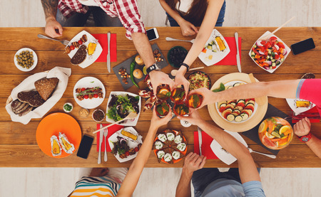clink: People clink glasses, saying cheers, eat healthy meals at party dinner table. Friends celebrate with organic food, ratatoille and corn barbecue on wooden table top view. Stock Photo