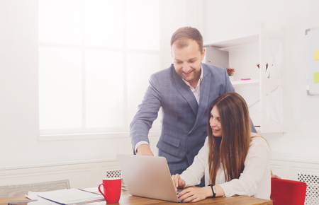 Businessman supervising his assistant's work on the laptop computer. Man helps woman in the office. Male boss and female secretary. Communication of manager and staff, checking job execution Stock fotó