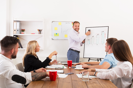 office presentation: Project presentation. Young happy businessmen and women at modern office, team corporate discussion at workplace, show information on board. Brainstorming and communication with partners for startup Stock Photo