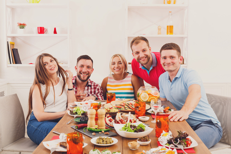 convivial: Group of happy young people posing at dinner table, party for friends indoors at cafe or home. Friendship, relax at holidays and week-end. Men and women sitting at table with various dishes. Stock Photo