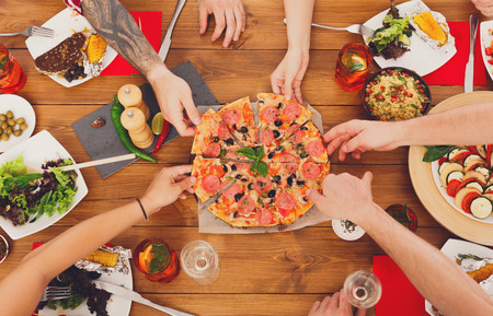 People eat pizza at festive table served for party. Friends celebrate with catering food on wooden table top view. Woman and mans yands take the pieces of italian pizza. Reklamní fotografie